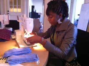 Tyra sewing reusable cloth menstrual pads at the FCF Raleigh office.